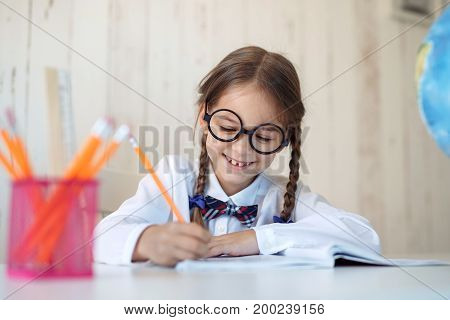 Hard-working little schoolgirl with two pigtails, wearing big glasses and school uniform, doing her homework while sitting at table, writing in copy book with happy expression. Children, education