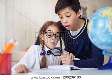 Two pupils staring through lens in book being surprised to see such big size of letters. Schoolgirl with pigtails, wearing big glasses and shirt having fun with her male friend while using magnifier