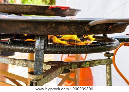 Open fire flame of gas burner with large flat paella jambalaya frying pan with cooking meal. Outdoors weekend picnic fest summer. Lifestyle nature.