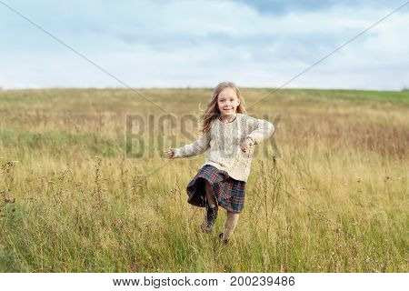 Little beautiful girl wearing warm sweater and skirt, running on green meadow, admiring fresh air, charming sky and nature. Pretty child posing on field. Children, relaxation, nature concept
