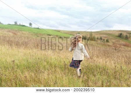 Back view of cute little girl with long luxuriant hair, dressed in knitted sweater and skirt, running on meadow, enjoying good time on nature, having relaxation. Lovely restful child on nature