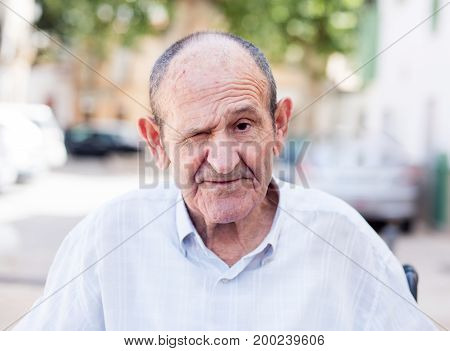 Portrait of an elderly man with one closed eye
