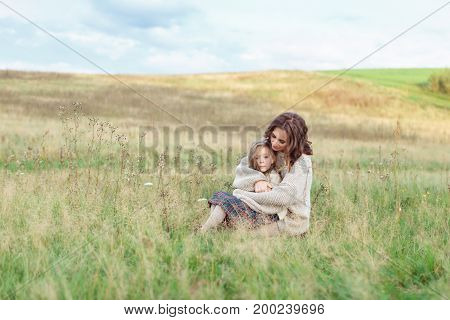 Pretty young woman in loose knitted swetaer embracing her little daughter while sitting together at grees grass, feeling relaxation, having good relatioships. Family, motherhood, rest concept