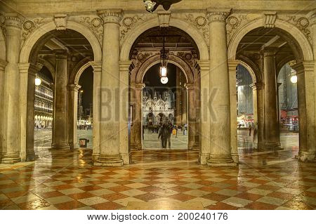 A passageway in Venice, Italy with arches.