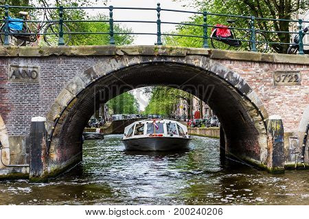 AMSTERDAM NETHERLANDS - 27 JULY 2017: Beautiful view of a canal boat under a bridge at the famous UNESCO world heritage canals of Amsterdam