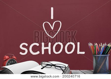 Digital composite of Books on the table against red blackboard with I love school text