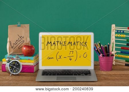 Digital composite of Computer on a school table with school icons on screen