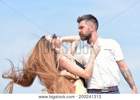 Relationship and love concept. Man with beard and woman with messy long hair waving on wind. Couple holds packets on blue background. Sexy girl and guy with serious face expressions hug each other