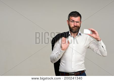 Success and business introduction concept. Guy with blank business card copy space. Businessman with disappointed face and glasses isolated on grey background. Man with beard holds white card