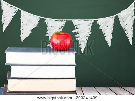 Digital composite of Books on the table against green blackboard with graphics