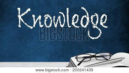 Digital composite of Desk foreground with blackboard graphics of knowledge