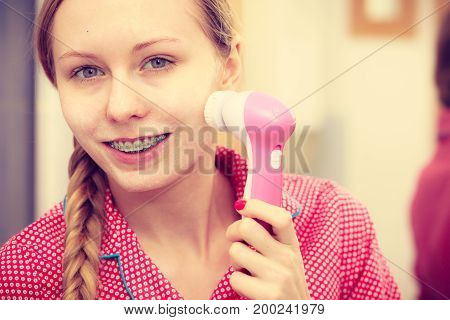 Woman Using Facial Cleansing Brush On Face