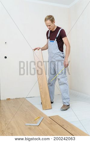 Installation of a laminate floorboard. The worker keeps a laminate floorboard for laying on the floor.