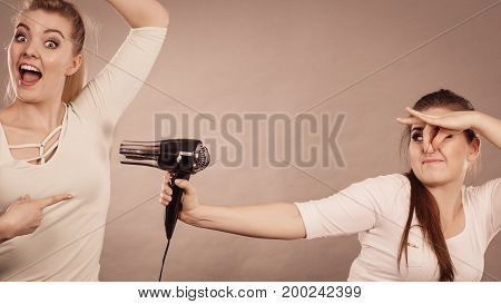 Woman drying her female friend wet armpit using hair dryer. Getting rid of sweat and bad smell hyperhidrosis. poster
