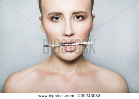 Young female patient with naked shoulders holds a syringe with beauty injections in her mouth on white background