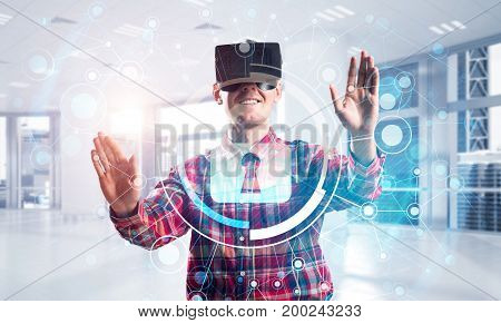Guy wearing checked shirt and virtual headset working with media screen panel. Mixed media