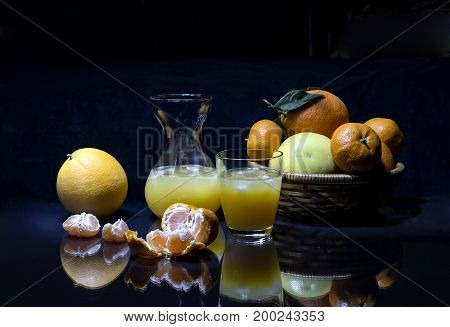 Pitcher and a glass of juice, oranges, grapefruit and tangerines on the table closeup