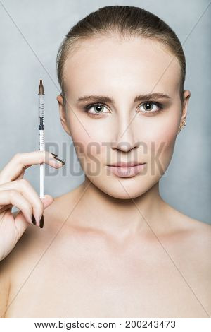 Close up portrait of a young female patient with nude make up and naked shoulders holds a syringe with beauty injections in her hand on white background.