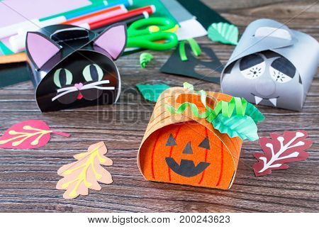 The Child Creates A Gift Box Of A Black Cat Of Halloween, A Halloween Pumpkin And A Vampire Box. Chi