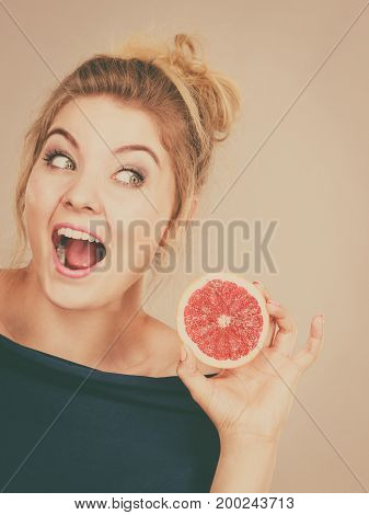 Healthy diet refreshing food full of vitamins. Happy woman holding sweet delicious citrus fruit red grapefruit.