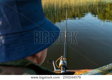 A Man Is Fishing From A Boat. View From Behind The Shoulder Of A Man, You Can See The Fishing Rod An