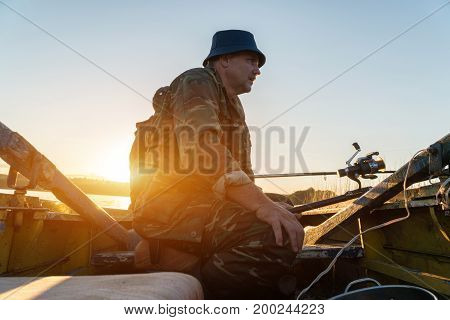 A Man Is Fishing From A Boat On Sunset