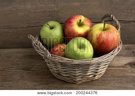 Basket of fresh apples on a wooden background