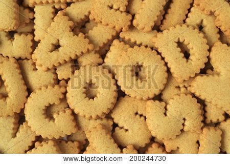 Top view of the word GOOD spelled with alphabet shaped biscuits on heap of the same biscuits