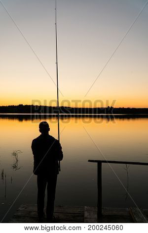 Silhouette Fisherman At Sunset. A Man Is Fishing From The Pier At Sunset
