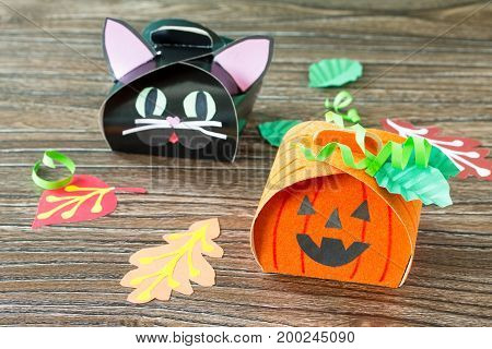 The Child Creates A Gift Box Of A Black Cat Of Halloween And A Pumpkin Of Halloween. Children's Art