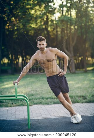 Man fitness model in shoes warming up outdoors
