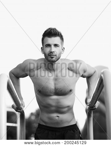 Muscle man making elevations outdoors. black and white photo