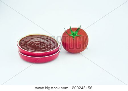 a cup of sauce and one tomato
