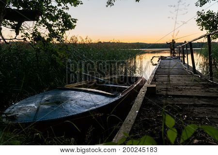 The Old Boat At The Pier At Sunset. In The Distance One Can See The Silhouette Of A Fisherman