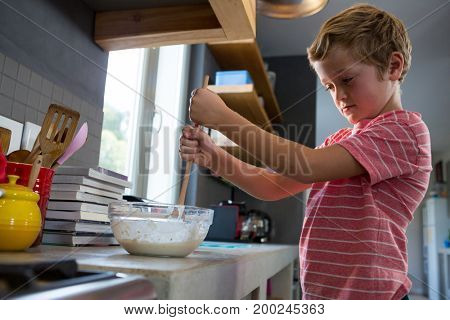 Boy mixing batter in kitchen at home