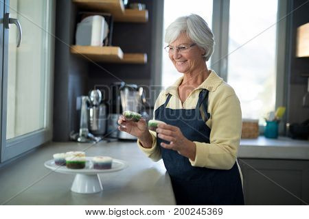 Senior woman picking up the cupcake from the tray in the kitchen