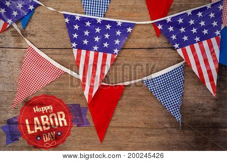 Happy labor day text in banner against high angle view of bunting flags on table
