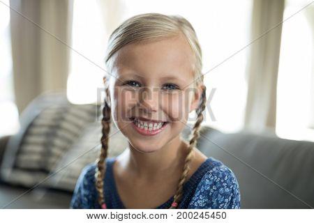 Portrait of smiling girl sitting on sofa in living room