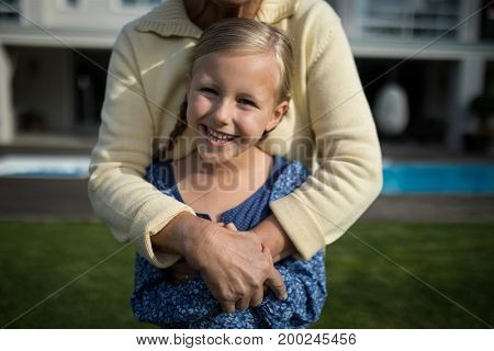 Portrait of smiling grandmother and granddaughter embracing each other in garden on a sunny day
