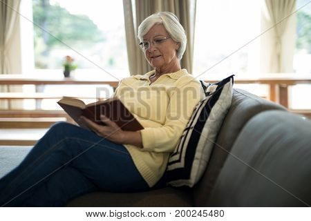 Senior woman reading book on sofa in living room at home