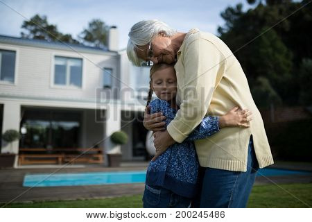 Grandmother and granddaughter embracing each other in garden on a sunny day