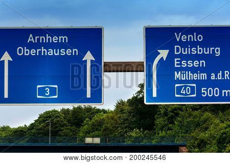 Highway sign directional sign on the motorway A 3 direction Venlo Duisburg Essen Muelheim an der Ruhr Oberhausen Arnhem and Highway crossing Kaiserberg.