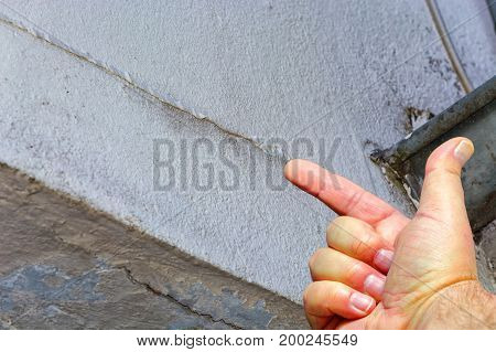 Human hand pointing at small cracks in plaster on the outside wall of a house. Building damage caused by weather.