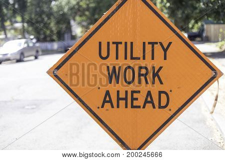 Orange utility work ahead sign that is off centered