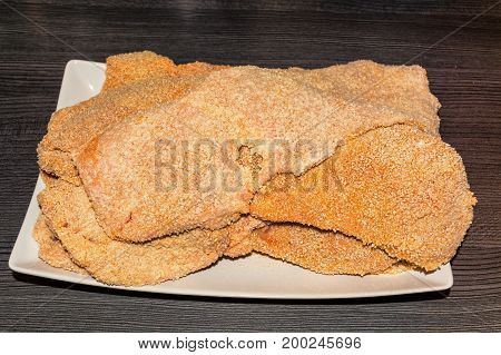Freshly baked raw escalope of veal on a white plate.