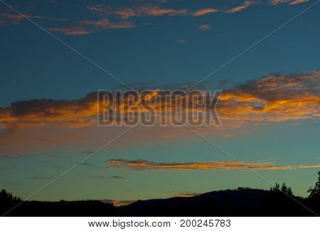 Country cloud formation at sunrise above mountain range with blue and green sky.