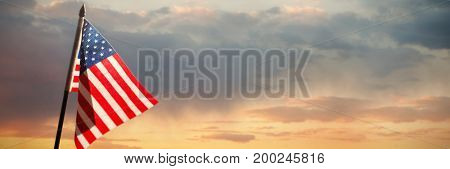 Close-up of American flag against scenic view of cloudy sky
