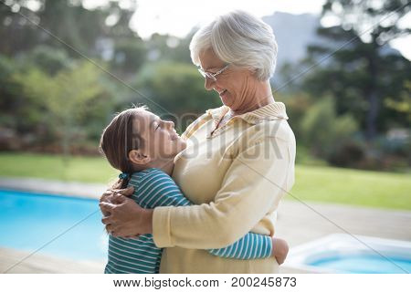 Loving granddaughter and grandmother embracing near the pool