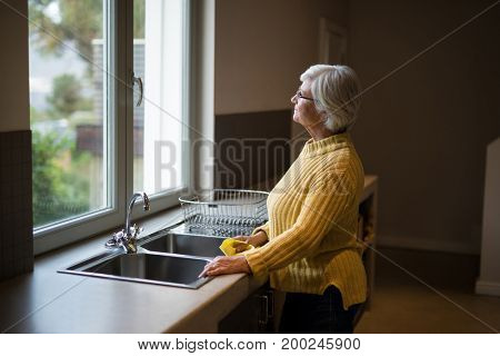 Thoughtful Senior woman standing near the kitchen sink and looking through window