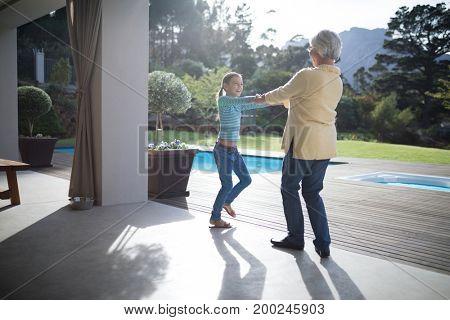 Playful granddaughter and grandmother enjoying near the pool